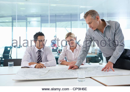 Business people reviewing map in conference room - Stock Photo