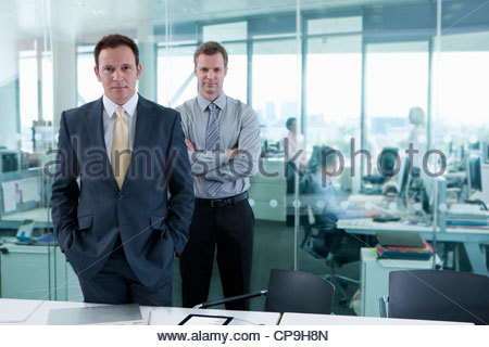 Portrait of serious businessmen standing in office - Stock Photo