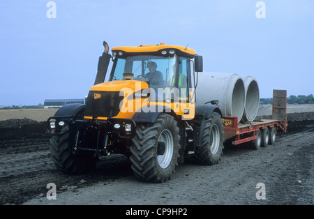 A 'JCB Fastrac 3220' Construction Vehicle towing concrete piping tubes over a land re-development site. - Stock Photo