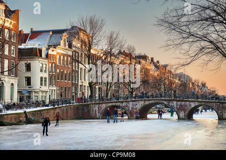 Skaters enjoy the ice on a winter evening on the Keizersgracht in Amsterdam, the Netherlands. - Stock Photo