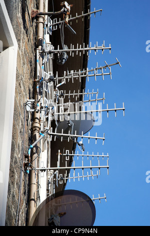 large amount of tv aerials and satellite receivers on a wall of a tenement building in Scotland uk - Stock Photo