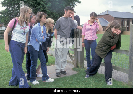 youths bullying young girl in park - Stock Photo