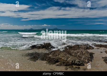 New Zealand North Island Waipu Cove Bream Bay rock and surf with volcanic islands in distance - Stock Photo