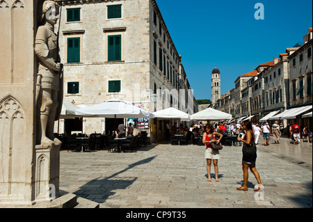 Tourist in front of the Orlando's column on Luza Square and the Stadrun in background , Old Town, Dubrovnik. Croatia. - Stock Photo