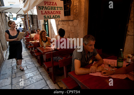 Outdoor dining in a Italian restaurant in a narrow street, Old Town, Dubrovnik. Croatia. - Stock Photo