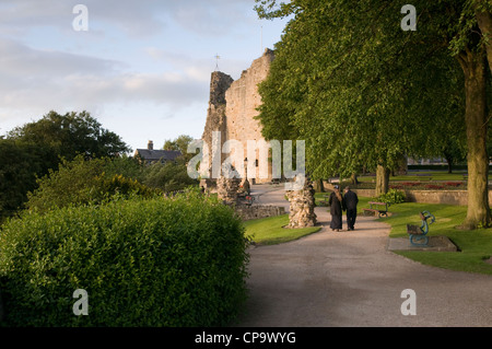 Two people walking together in summer evening sun, in park near medieval tower keep & ruins of Knaresborough Castle - Stock Photo