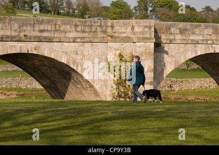 Walking a dog near the bridge over the River Wharfe, Burnsall. - Stock Photo