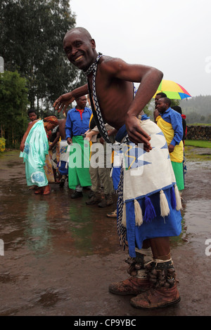 A man dances in the rain at the Iby'lwacu Cultural Village on the edge of the Volcanoes National Park, Rwanda. - Stock Photo