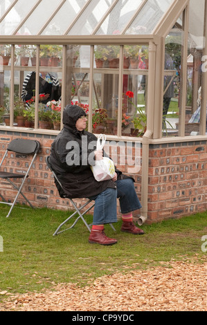 Sitting in rain (waterproof coat hood up) lady is wet & miserable on day out (by trade stand greenhouse) - RHS Tatton - Stock Photo