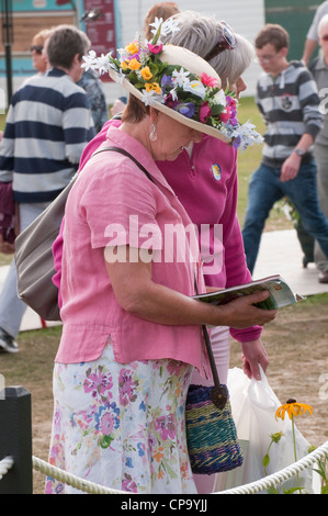 Close-up of lady wearing straw hat decorated with colourful summer flowers, standing & reading guide book - RHS - Stock Photo