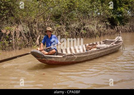 Vietnamese man rowing a long boat, Cai Be, Mekong River Delta, Vietnam - Stock Photo