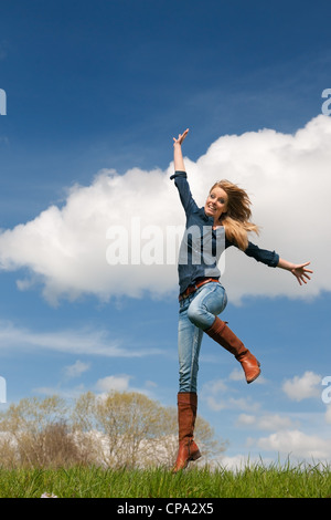 Jumping young blond girl with blue sky and grass - Stock Photo