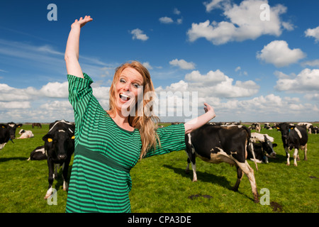 Young blond Dutch girl happy in farm field with black and white cows - Stock Photo