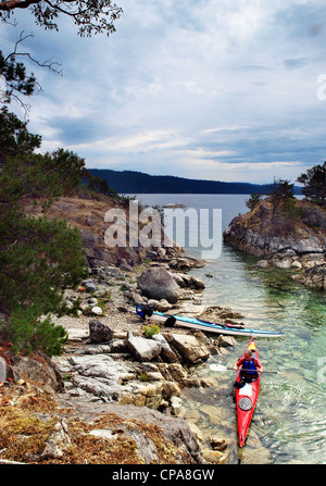 A sea kayaker paddling through The Curme Islands in Desolation Sound, British Columbia - Stock Photo
