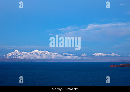 The Island of the Moon in Lake Titicaca in Bolivia at sunset with the snowy Andes Mountains behind, as seen from - Stock Photo