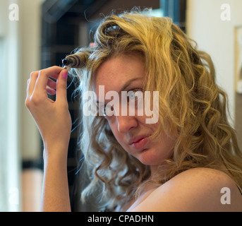 Mariel West, 24, uses a curling iron to curl her hair. - Stock Photo