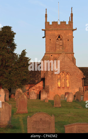Church and Churchyard glowing in the early morning sun. Cotswolds in Southwestern England - Stock Photo
