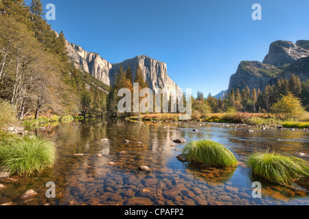 A river runs through the mountainous, forested landscape of Yosemite National Park in California in sunshine - Stock Photo