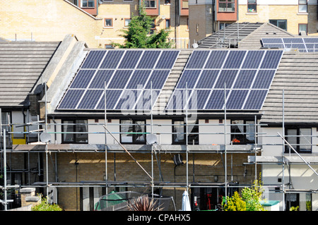 Scaffolding for solar energy power cell panels installation on roof of modern house for cheaper electricity Silvertown - Stock Photo