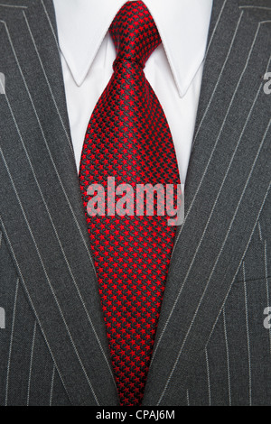 Photo of a grey pinstripe suit with plain white shirt and red patterned tie - Stock Photo