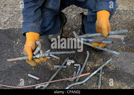 Man Handling Scrap Copper in a Scrap Metal Yard. UK. - Stock Photo