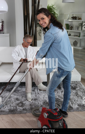 Girl vacuuming and senior woman reading a book - Stock Photo