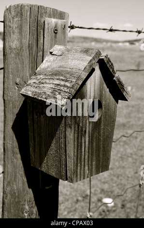 Wooden bird house on a barbwire fence. - Stock Photo