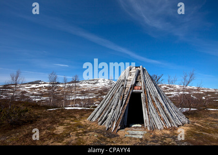 A goahti / kota, traditional Sami wooden hut on the tundra in spring, Lapland, Sweden - Stock Photo