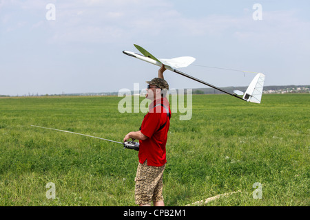 Man launches into the blue sky RC glider - Stock Photo