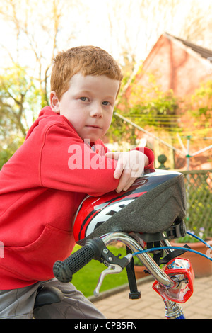 Little boy on his bike in his garden, looking to camera. - Stock Photo