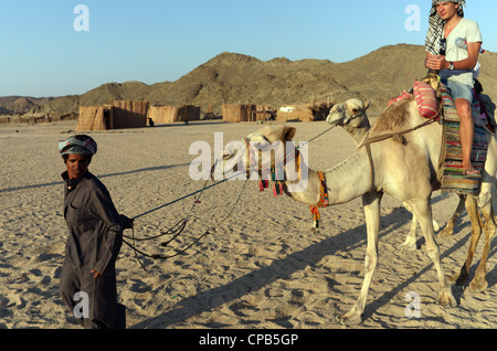Bedouin guide in traditional clothing leads tourists riding camels in desert. Bedouin village about Hurghada, Egypt, - Stock Photo