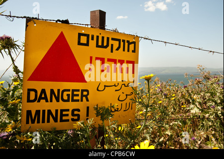 A sign reading 'Danger Mines!' hangs from a barbed wire fence in the Israeli occupied Golan Heights. - Stock Photo
