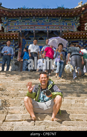A local Chinese tourist poses for the camera outside the 12 Generals Temple at Mount Kongtong near Pingliang city - Stock Photo