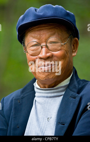 A elderly Chinese man dressed in traditional clothes with round spectacles pose for the camera in Pingliang. - Stock Photo