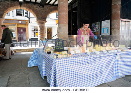 Cheese stall in the Market House, Ross on Wye, Herefordshire, UK. Woman selling cheese. - Stock Photo