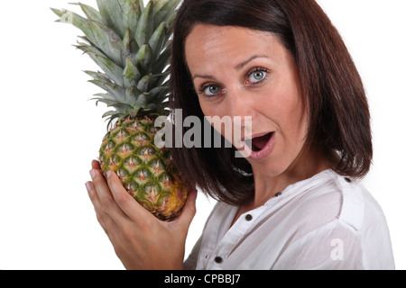 portrait of a woman holding a pineapple - Stock Photo