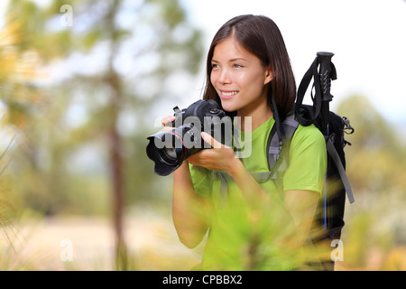 Young beautiful mixed race Chinese Asian / Caucasian female hiker photographing through professional SLR camera - Stock Photo