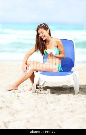 Beautiful young mixed race woman in bikini applying sunscreen lotion on legs sitting on sunbed on Varadero Beach, - Stock Photo