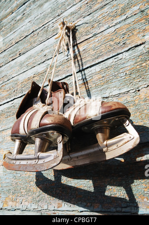 vintage pair of mens ice skates hanging on a wooden wall Stock Photo