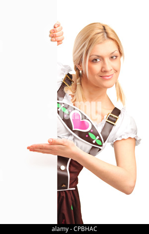A portrait of a woman in traditional bavarian costume holding a white panel isolated on white background - Stock Photo
