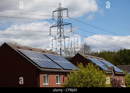 Solar panels on houses with electricity pylons behind, Wales, UK - Stock Photo