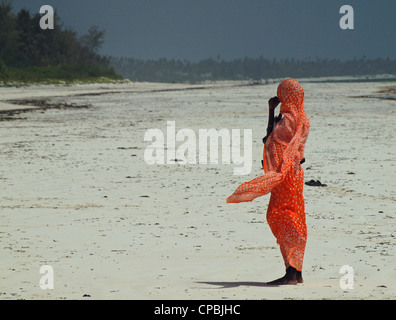 local swahili woman standing on a white sandy beach in Zanzibar, in heat haze with sea breeze fluttering her colourful - Stock Photo