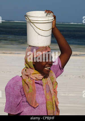 local Swahili woman in colourful traditional costume laughing on a white sandy beach in Zanzibar, carrying white - Stock Photo