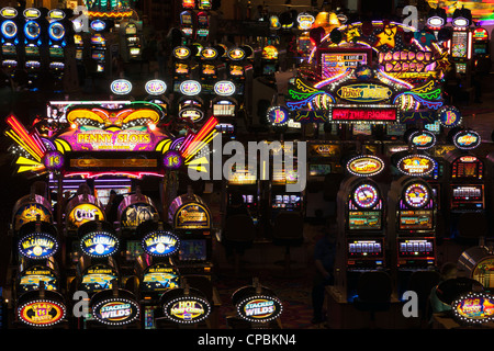 Slot machine games and gambling games in a dark casino floor, Las Vegas, Nevada. Tourists playing and hoping to - Stock Photo