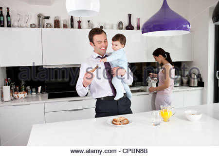 A father trying to eat his breakfast whilst holding his baby son - Stock Photo