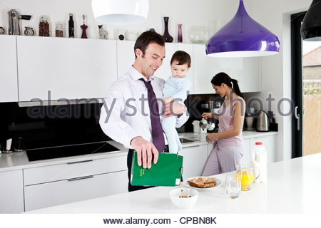A father holding his baby son whilst making breakfast - Stock Photo