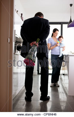 A man returning home to his family after work, holding a bunch of roses - Stock Photo