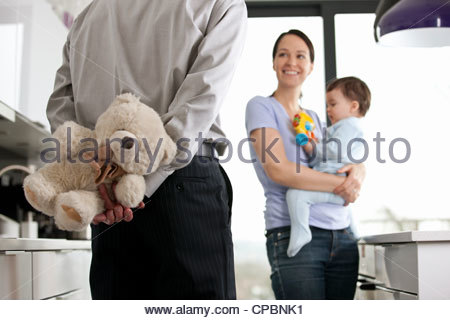 A man returning home to his family after work, holding a teddy bear behind his back - Stock Photo