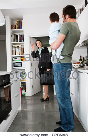 A mother leaving for work, waving goodbye to her partner and baby son - Stock Photo