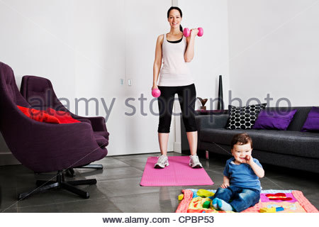 A young mother exercising at home whilst her baby son plays on the floor - Stock Photo